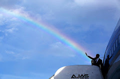 President Obama waving from airplane with rainbow behind him