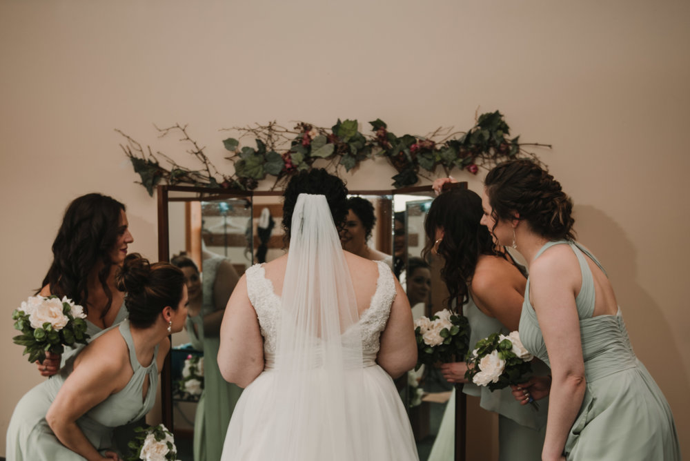 Bride and bridesmaids looking at bride in the mirror.