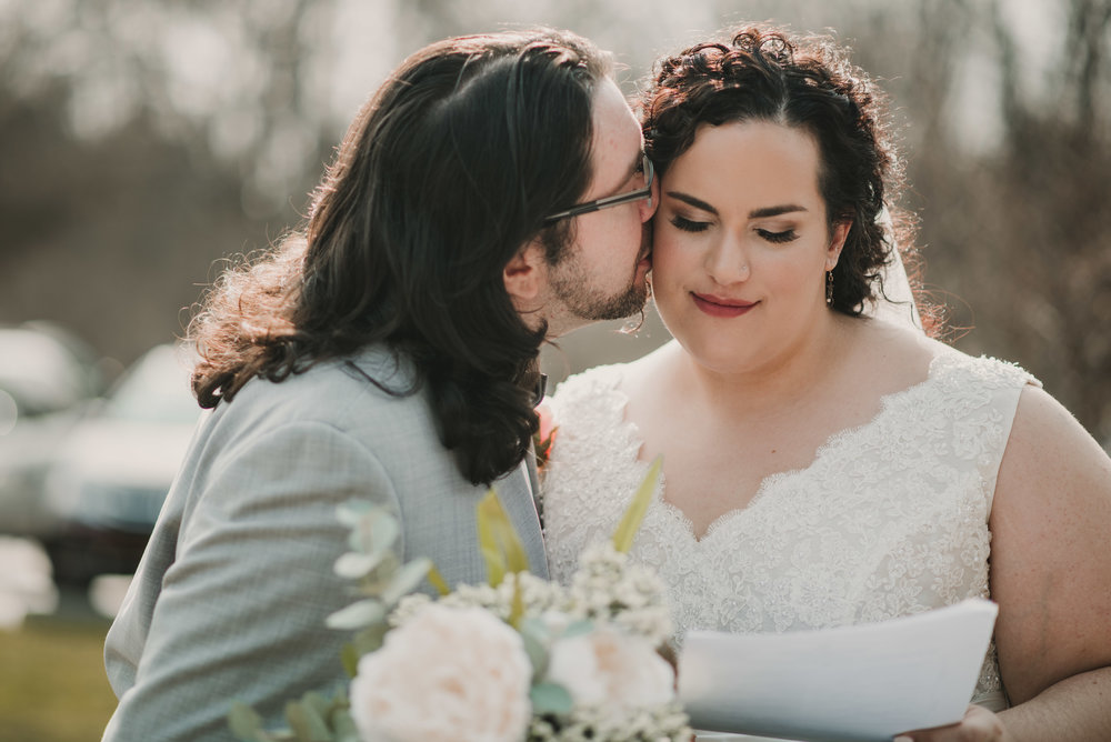 Groom kissing bride on the cheek after signing marriage license