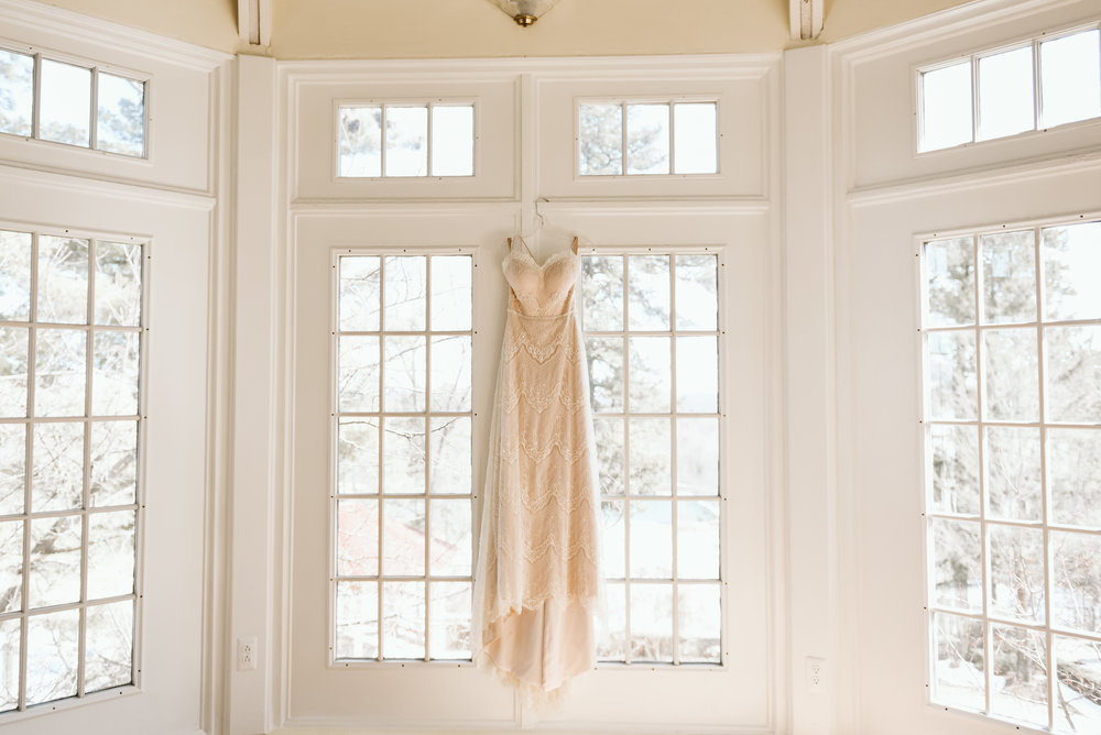 brides dress hanging up on the window