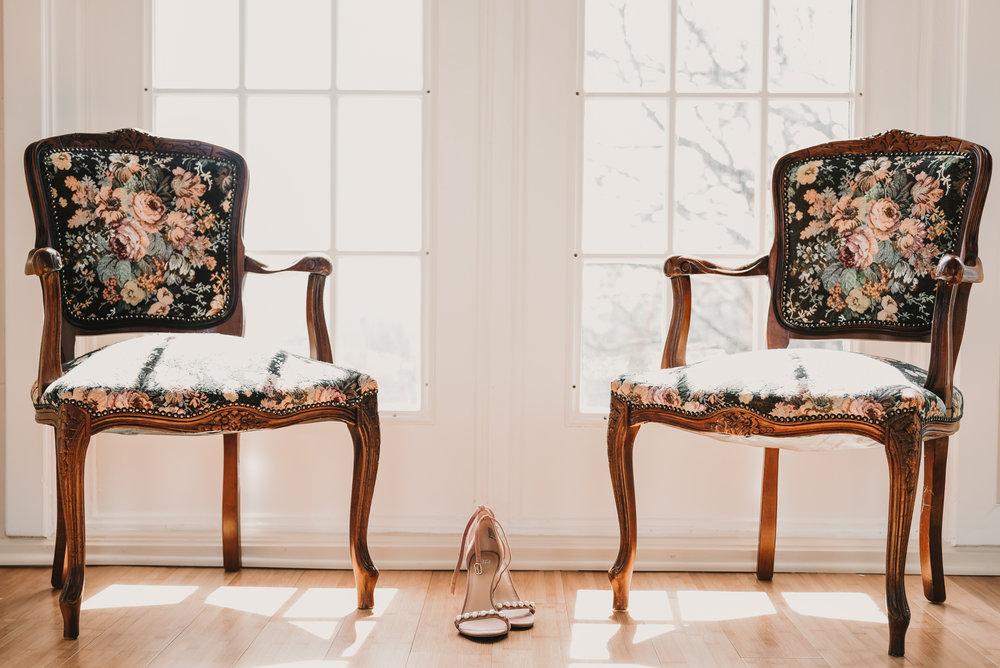 brides shoes in between two chairs