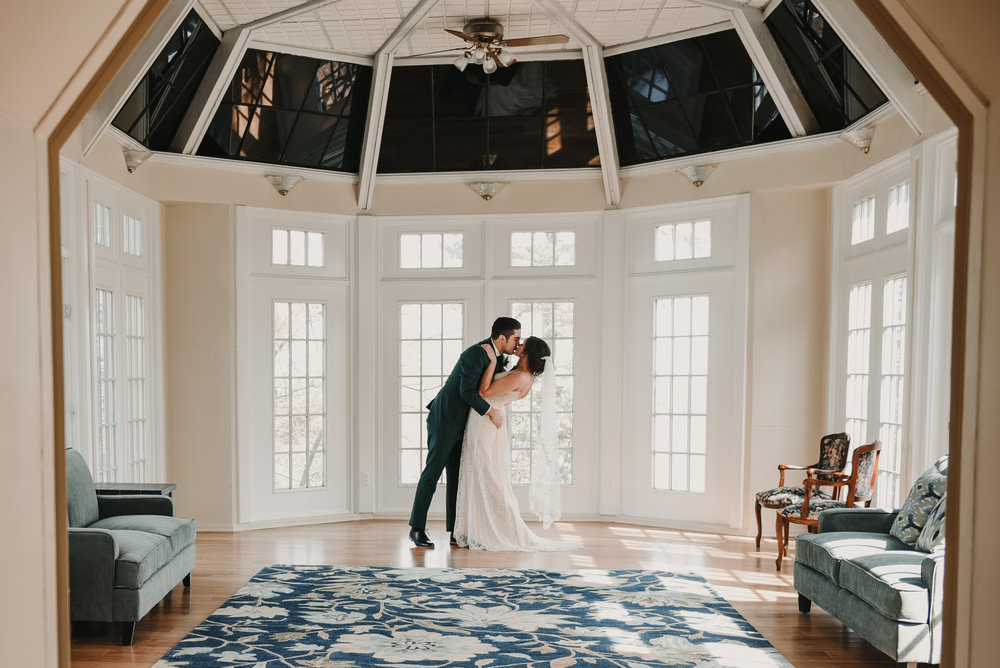 Bride and groom kissing by the window