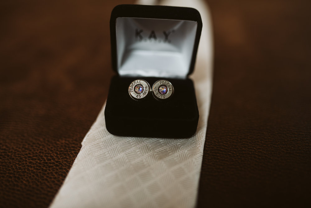 Grooms cuff links on top of grooms tie