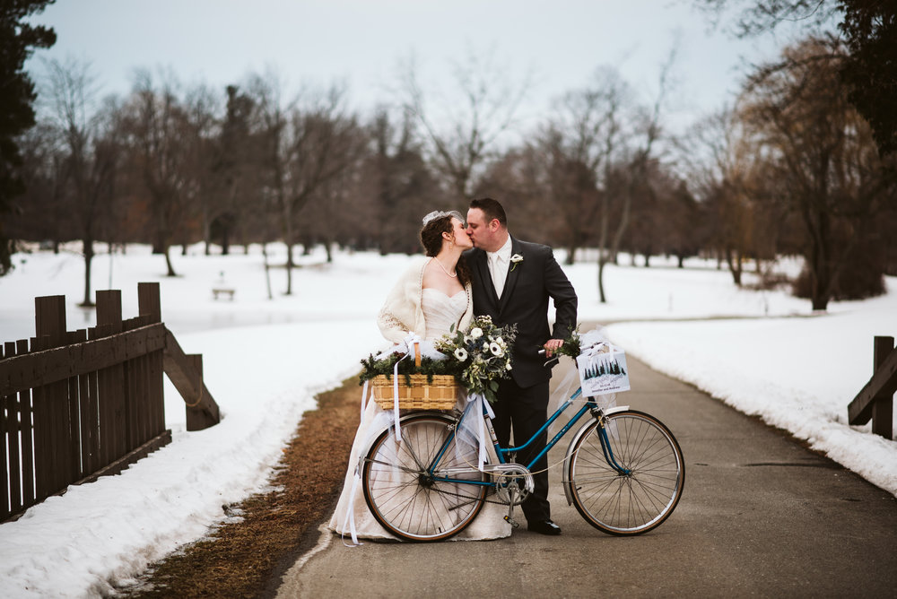 Bride and groom kissing  behind bicycle.