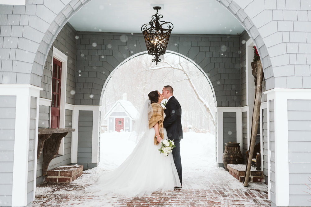 Bride and groom kissing under archway during snow storm
