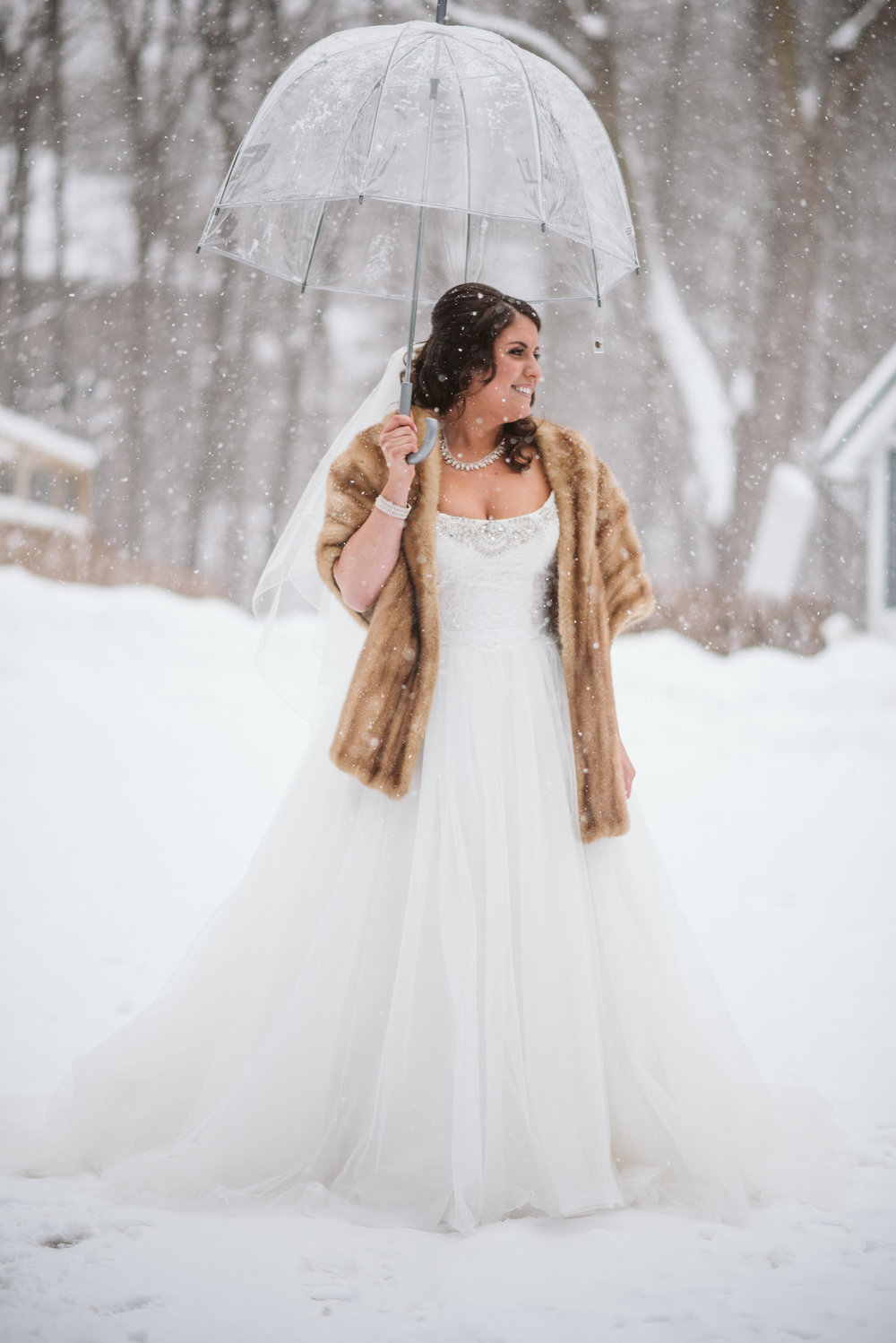Bride under umbrella in the snow