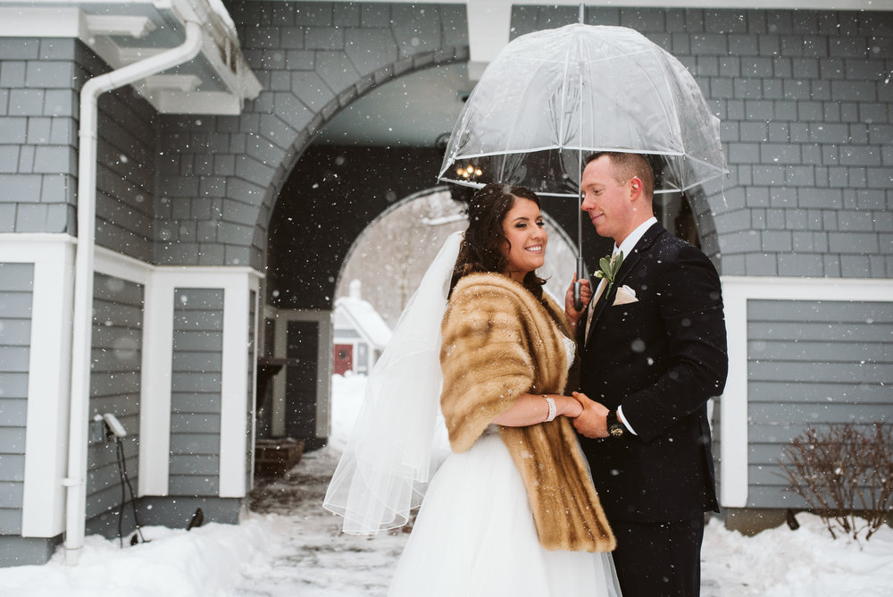 Bride and groom under umbrella during snow storm