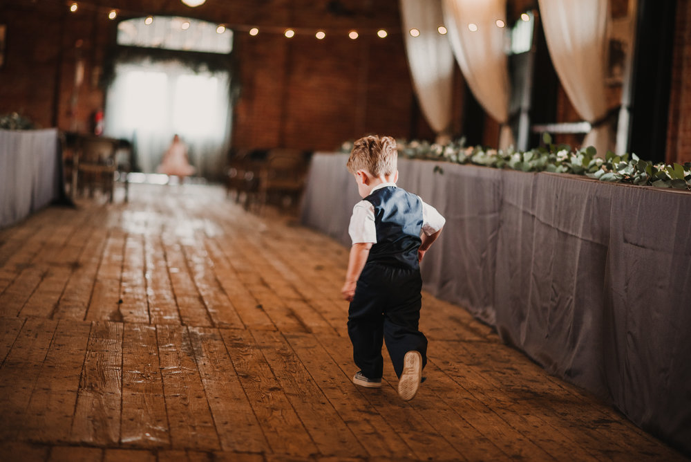 Ring bearer running down the aisle .