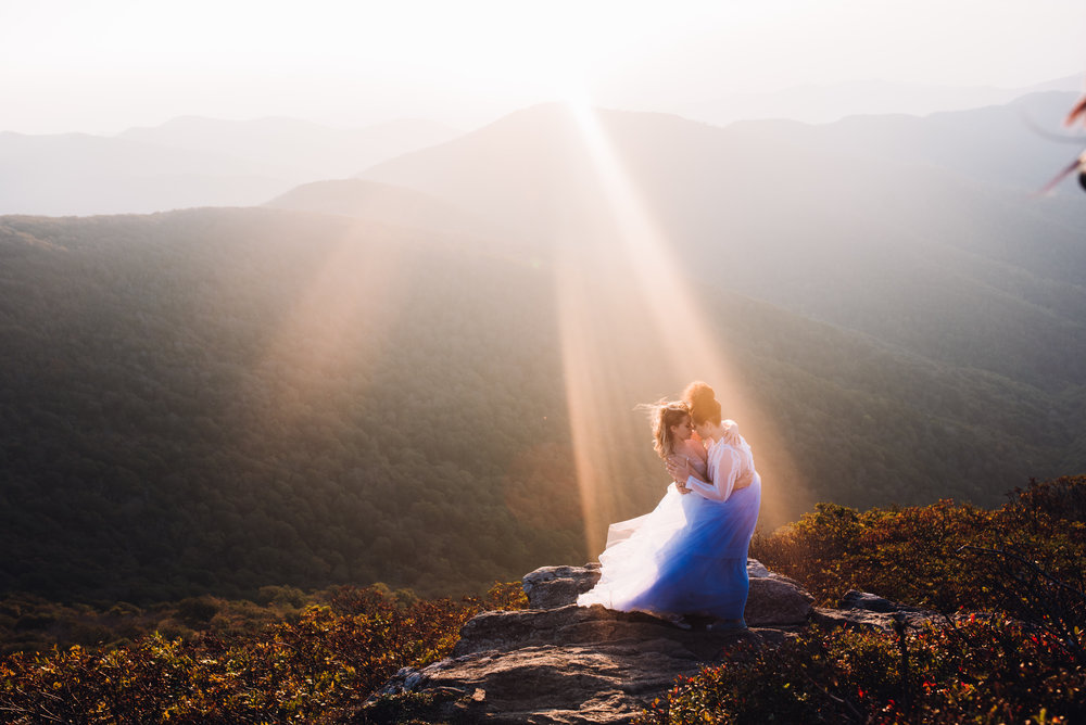 Bride and Bride share a kiss during sunset on the mountain.
