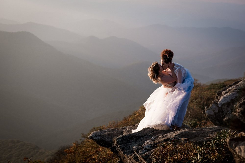 Bride and bride share a kiss during sunset on the mountain