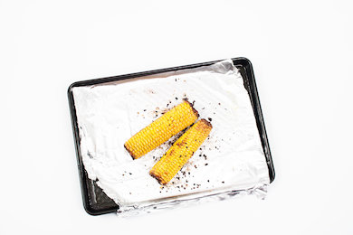 Preheat the oven to 200C, place the corn on a roasting tin with olive oil, salt, pepper and  chilli flakes   . Cook in the oven for 35 minutes turning every 10 minutes.