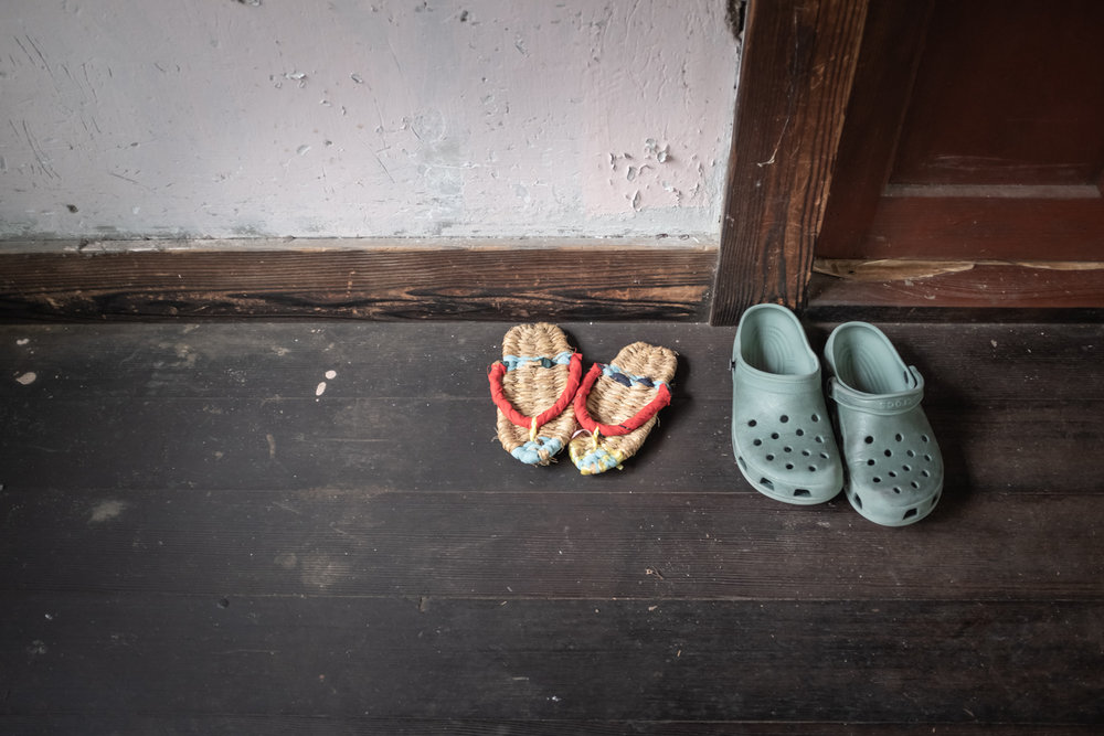 A pair of zōri (Japanese sandals) and a pair of crocks, indoors corridor.