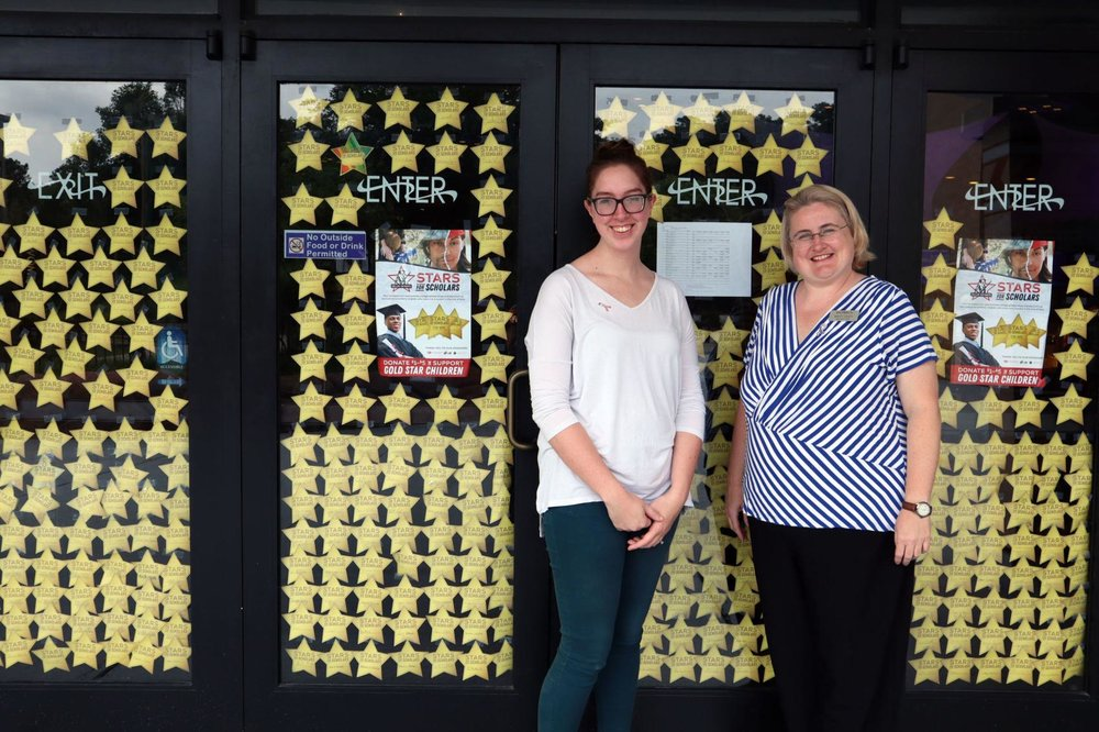 From left, Rachel Eisenbrandt and Britt Argo, stand in front of the 'Stars for Scholars' sign posted on the doors of Aurora Cineplex in Roswell. Both Eisenbrandt and Argo, who work at the theatre, have family members who served in the armed forces.   Lindsay Moscarello