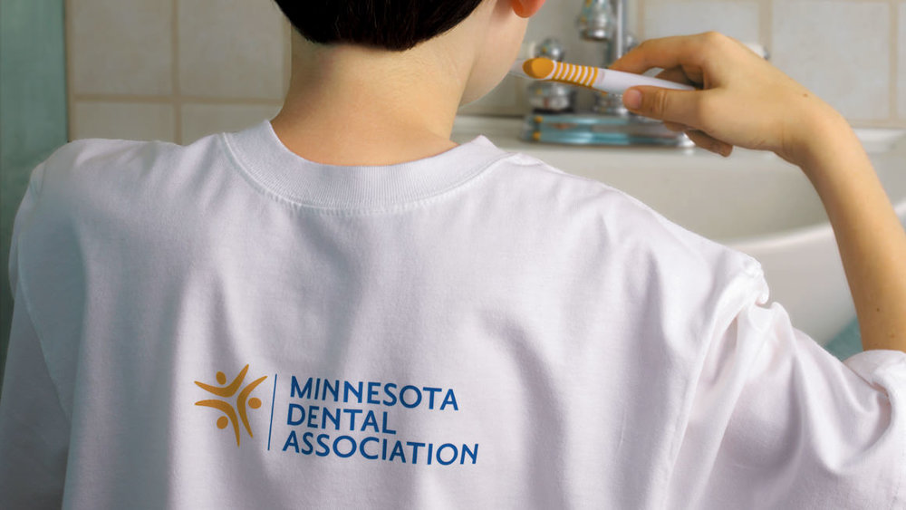 Young boy brushing his teeth with a Minnesota Dental Association logo on the back of his t-shirt