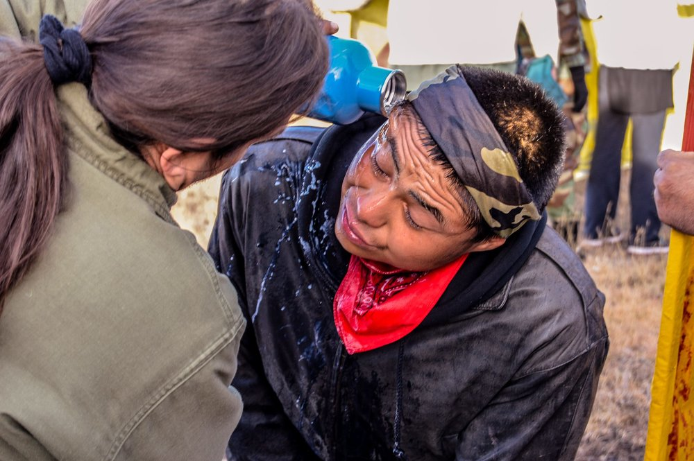 22 Oct 2016. A Water Protector being rinsed off after Police OC sprayed him without provocation 3 miles west of Highway 1806. Photo by   Rob Wilson Photography