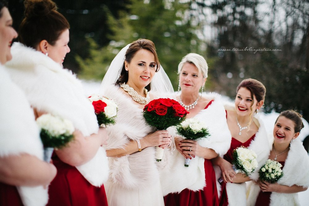 Happy snowy bridal party with red dress and accents.