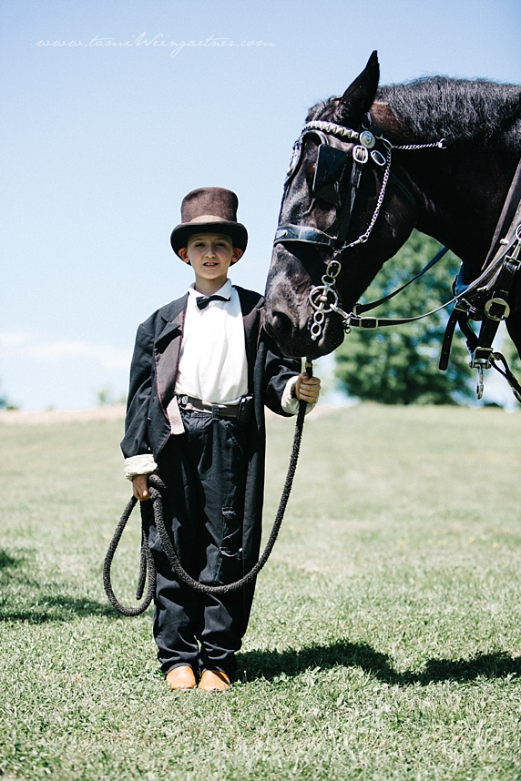 Young ring bearer holding a horse during a wedding ceremony