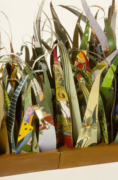 close up of blades of grass cut from recycled tin cans