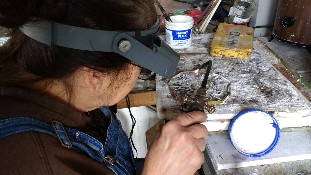 Artist Harriete Estel Berman soldering the frame around the Web of Lies Bracelet   (above.)    This frame was a lot more work but it will add structural integrity to the thin bracelet, and on display the cut out lettering will float above the pedestal.