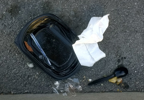 Black plastic take-out tray, black plastic spoon, and cellophane in the street.