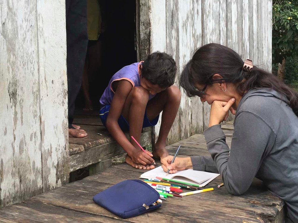 Alejandra takes notes with a family in Comunidade Deus e Pai.