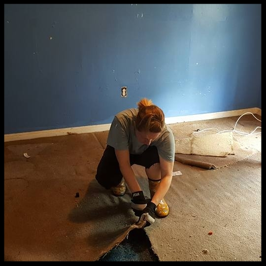 One of our volunteers removing flood damaged carpet