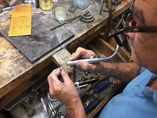 One of our jewelers polishes a custom-made gent's wedding band. Work with our staff to ensure that your jewelry is manufactured to your liking.