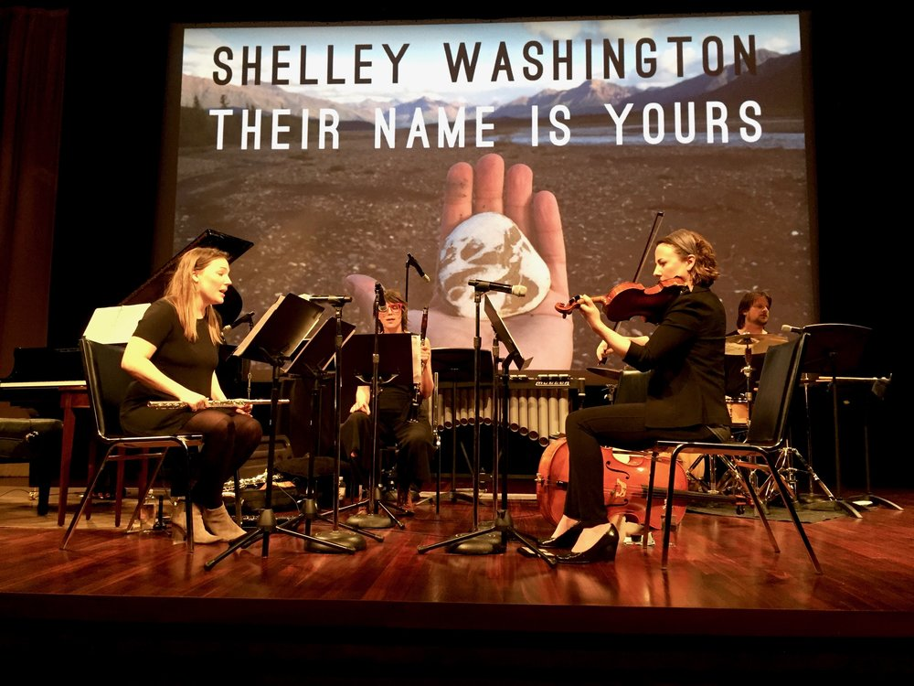 "Musicians and leaders of  Wild Shore New Music ,  Katie Cox  playing flute (left),  Andie Tanning Springer  on fiddle (right), with   Christa Van Alstine  on clarinet (center) and  Michael McCurdy  on drum set (far right) performing ""Their Name Is Yours"" at the  U.S. National Archives  on March 30th, 2017."