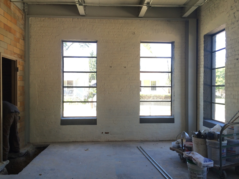 Windows are painted! And there are large holes in the floor for plumbing. Painting the walls is next.