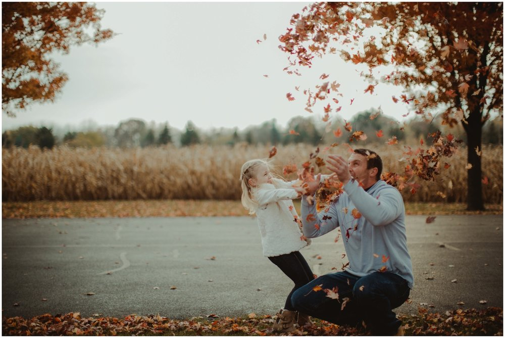 Milwaukee Family Photographer | Daddy and Daughter Fall Session | Dad and daughter leaf fight.