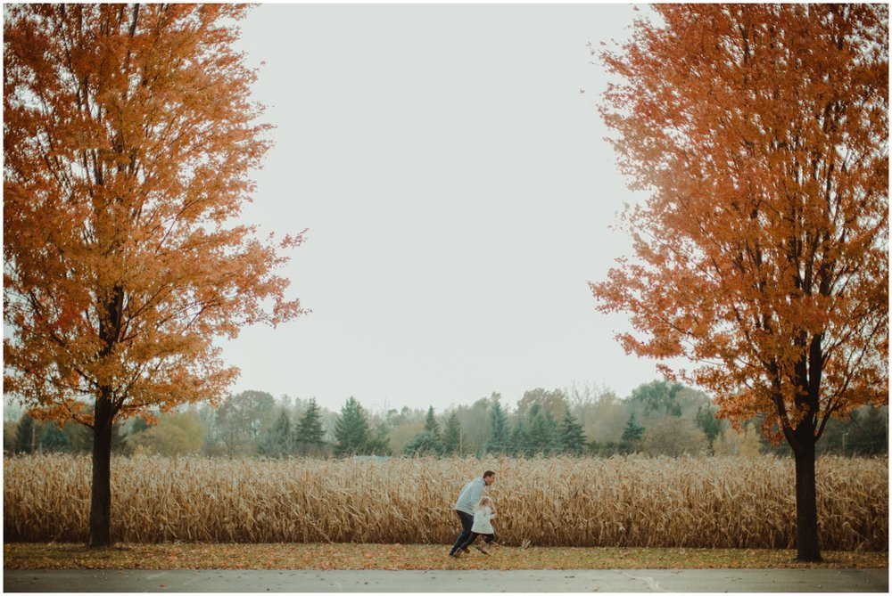 Milwaukee Family Photographer | Daddy and Daughter Fall Session | Dad chasing daughter next to cornfield.