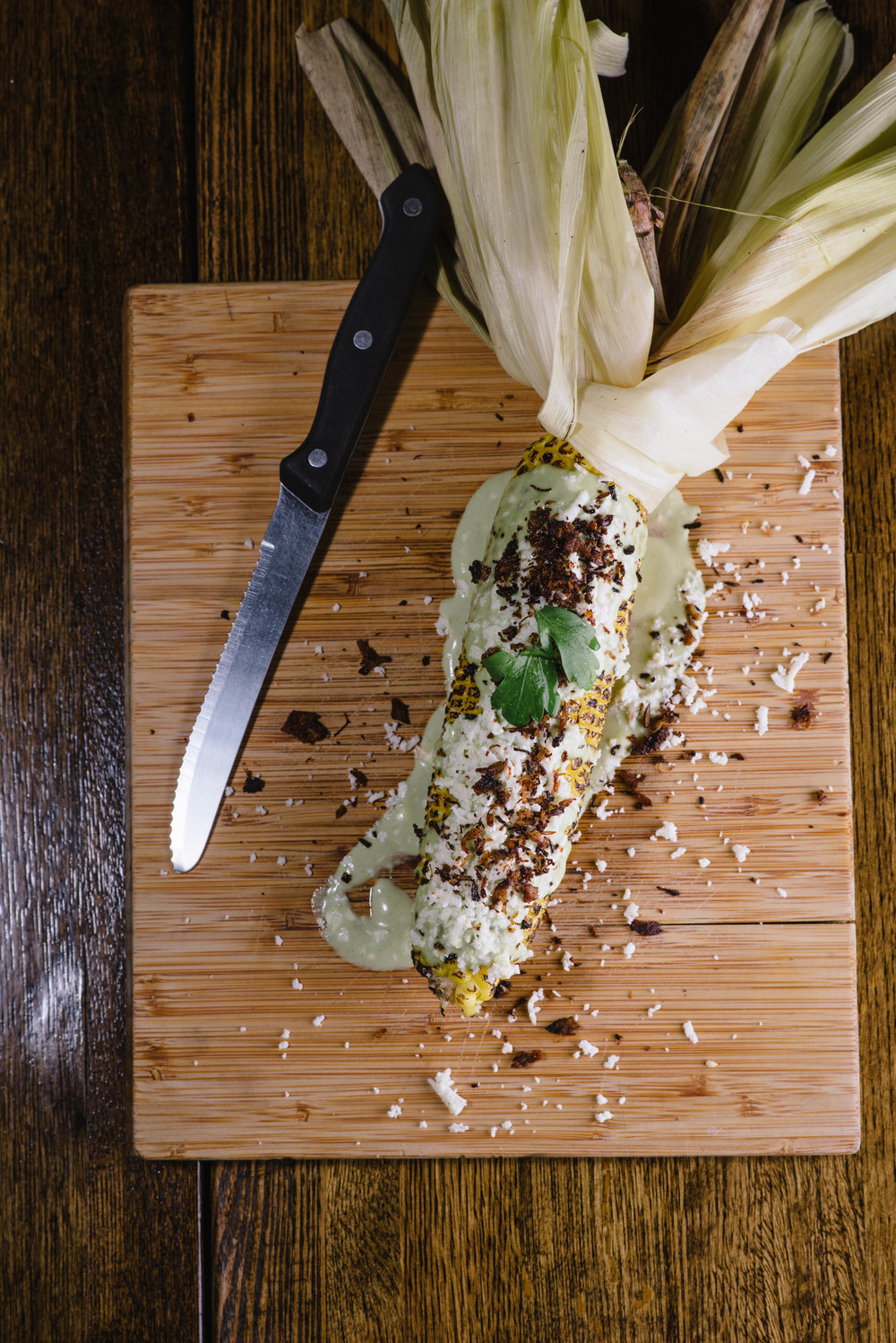"Choclo Asado con Queso: Charcoal grilled white corn topped with ""mapahuira"" (roasted pork pieces), cilantro avocado cream sauce, and queso fresco."