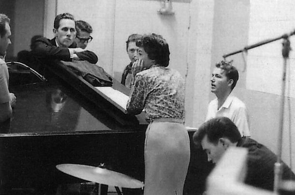 RCA studio session of Nashville musicians, from left: Bob Moore, Chet Atkins (arms folded on piano), Louis Nunley, Gil Wright, Anita Kerr (leaning on piano, back to camera), Willie Ackerman, and Floyd Cramer.
