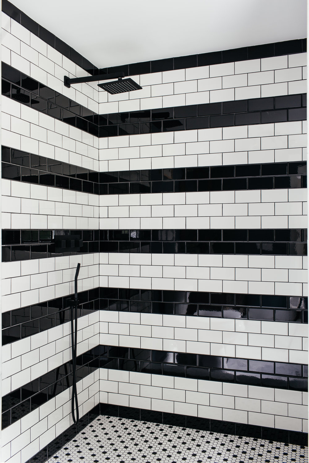 black and white striped subway tile shower in master bath designed by The Rath Project