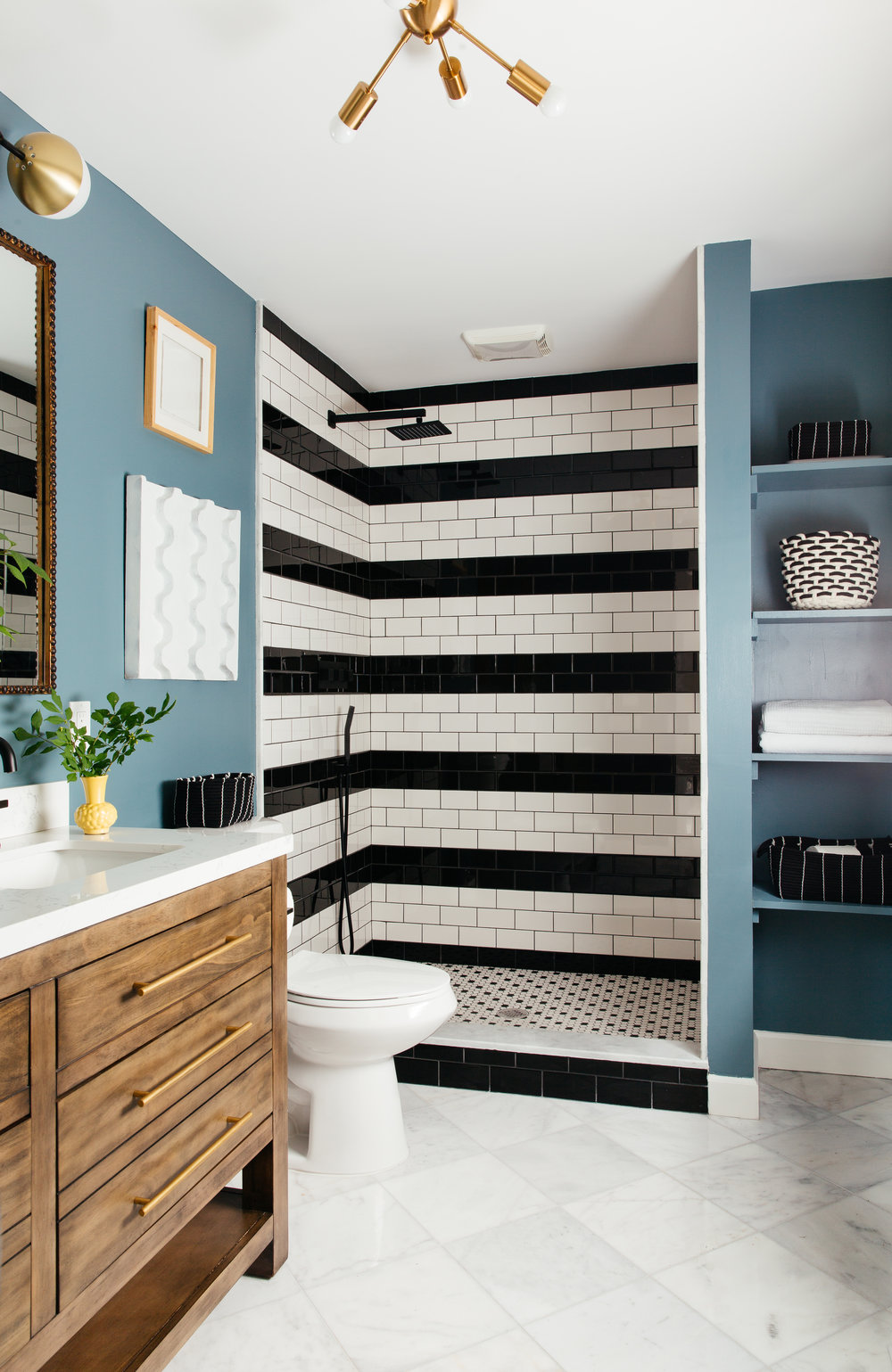 black and white striped subway tile shower in modern master bath with marble floor designed by The Rath Project