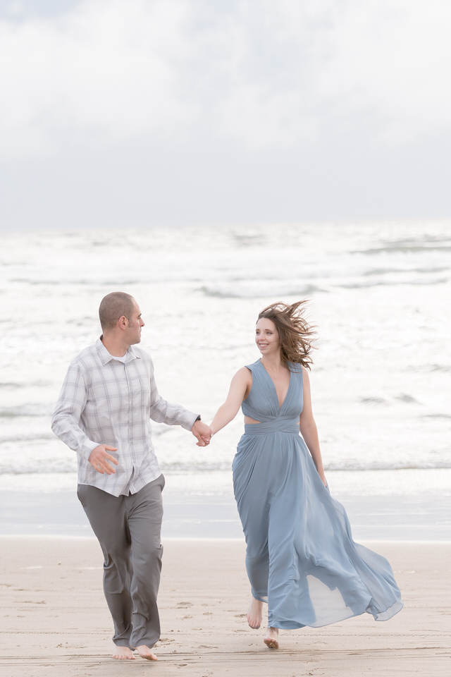 Couple running on the beach in gown romantic engagement