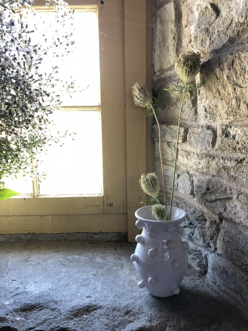 bauble vase with queen anne's lace in barn window