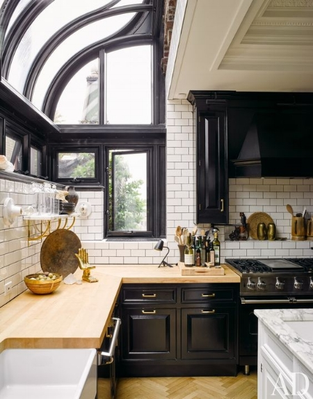 Black kitchen cabinetry and window interiors get warmed up by the wood herringbone floors and butcher block countertops. Image via Architectural Digest