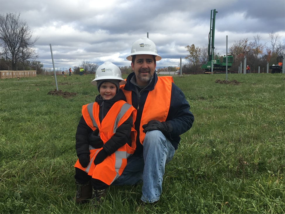 United Renewable Energy LLC CEO William Silva of Somerville and son Billy, 4, during post pounding at Somerville Community Solar Farm, the first step to building racking for the solar panels. (photo provided)