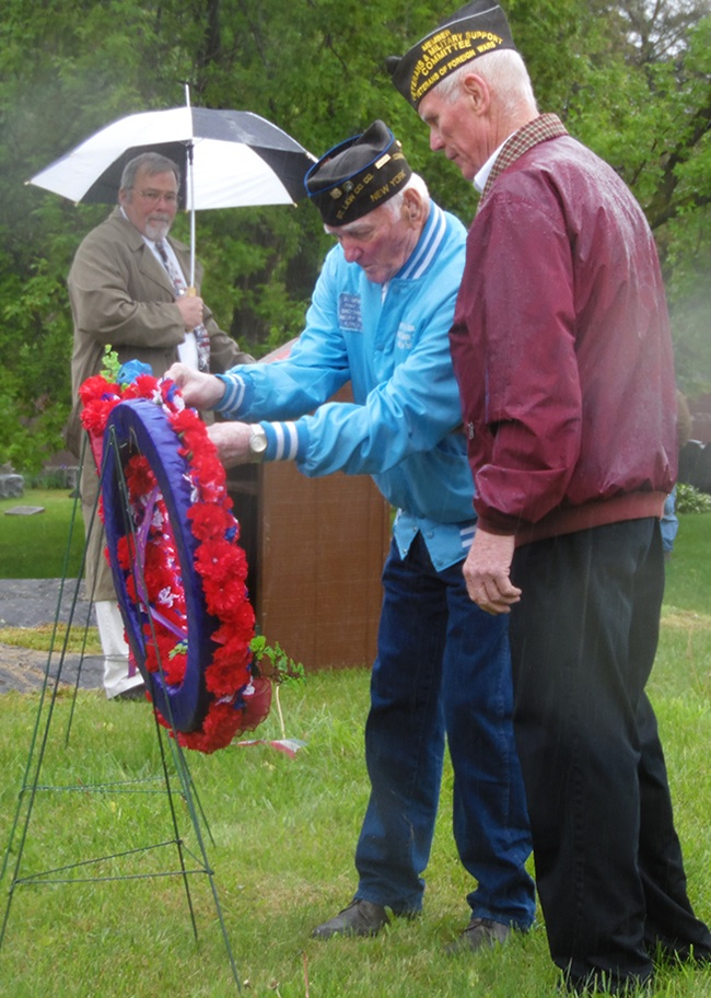 Al Melisko placing the ribbon to remember those who lost their lives in Korea. Also pictured is Mike Webster (right) who served as an escort during the ceremony and (behind) Master of Ceremonies Jim Wright. (Rachel Hunter photo)