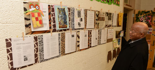 Dr. Comer admires student work showcased on the wall of Thornwell