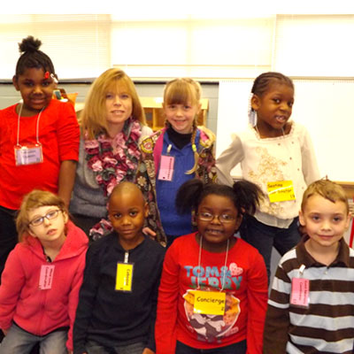 Teacher Nancy Williamson, second from left in the back, poses with some of her employees. The kindergartners are proud of their jobs and badges