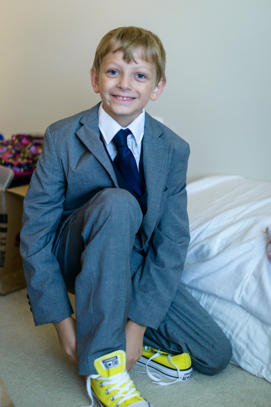 A young ring bearer puts on yellow sneakers with his suit before the wedding at a home in fairfax, virginia