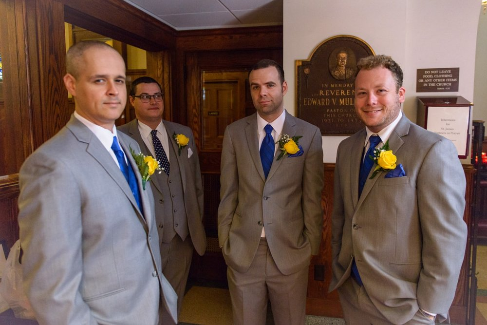 Groomsmen and the groom in the back of St James Catholic Church before the wedding in Falls Church, Virginia