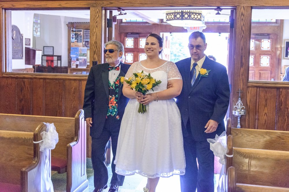 The bride walking in with her father and stepfather holding bright yellow flowers at St James Catholic Church in Falls Church, Virginia