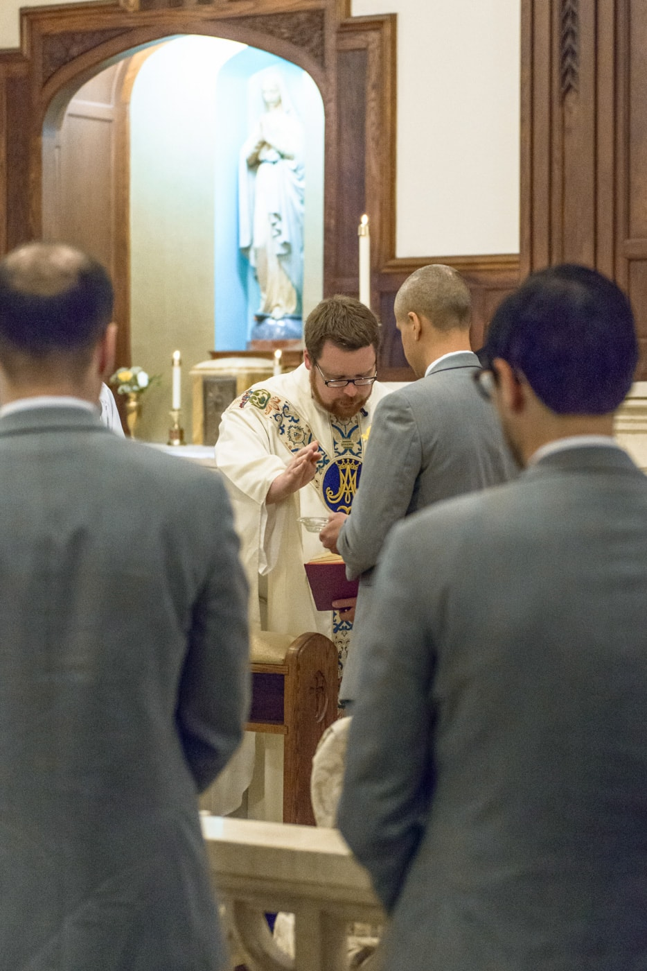 The priest blesses the rings during a wedding ceremony at St James Catholic Church in Falls Church, Virginia