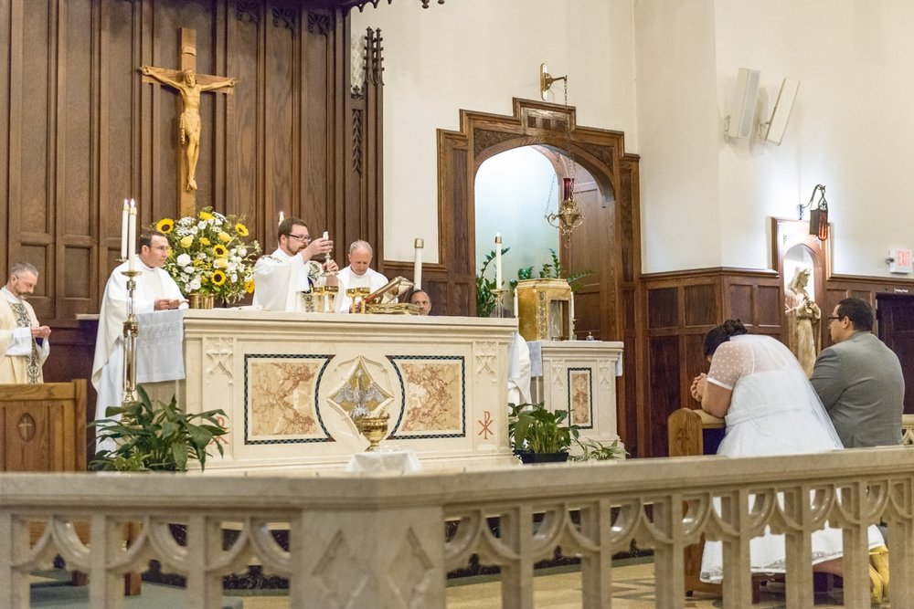 A prayerful bride and groom kneel before the altar during Catholic mass wedding ceremony at St James Catholic Church in Falls Church, Virginia