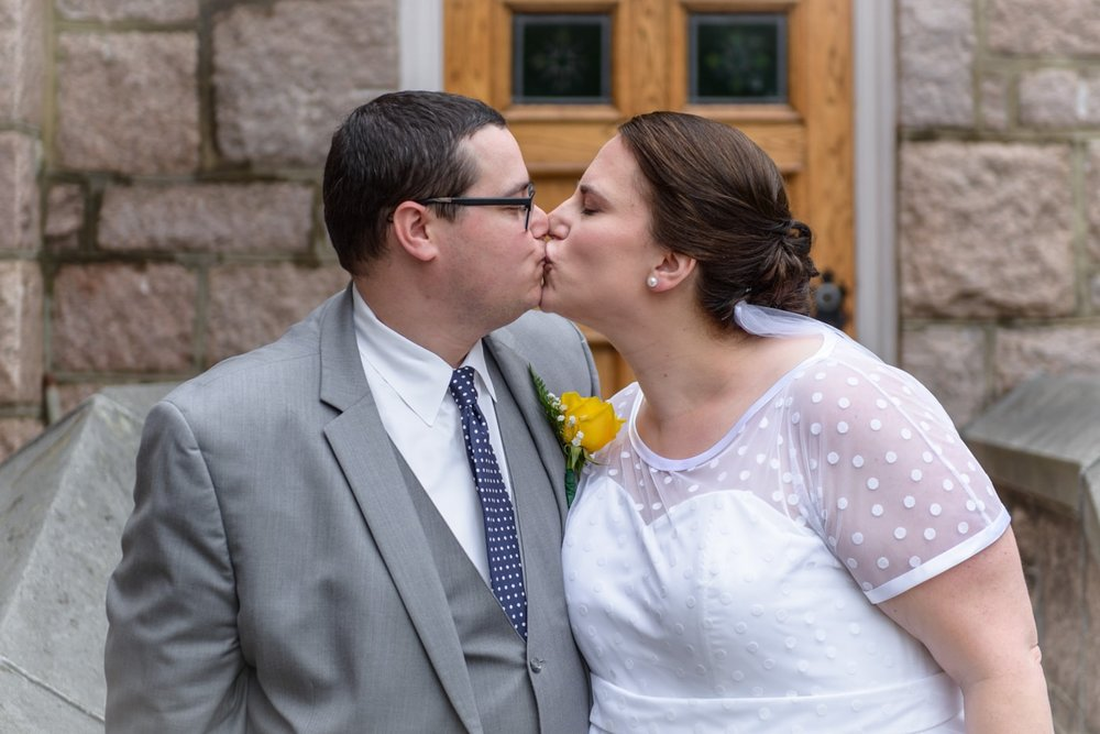 The bride and groom kiss outside St James Catholic Church in Falls Church, Virginia