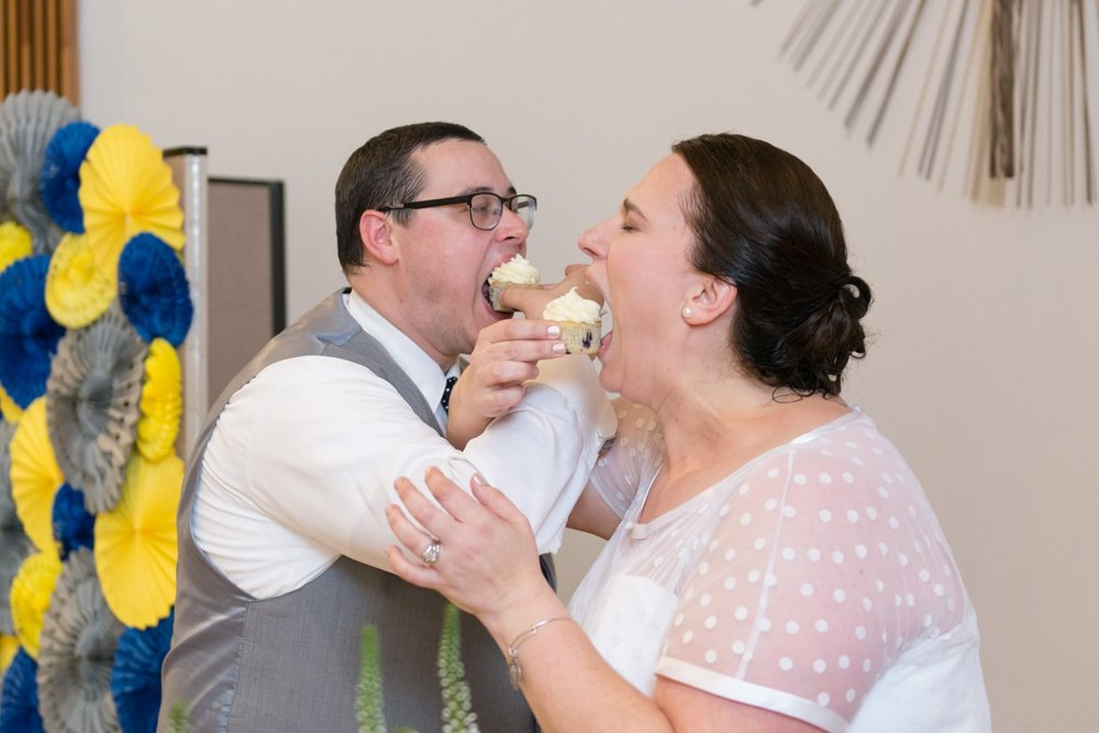 The bride and groom lock arms and eat cupcakes at their wedding reception at St Mark Catholic Church in Vienna, Virginia