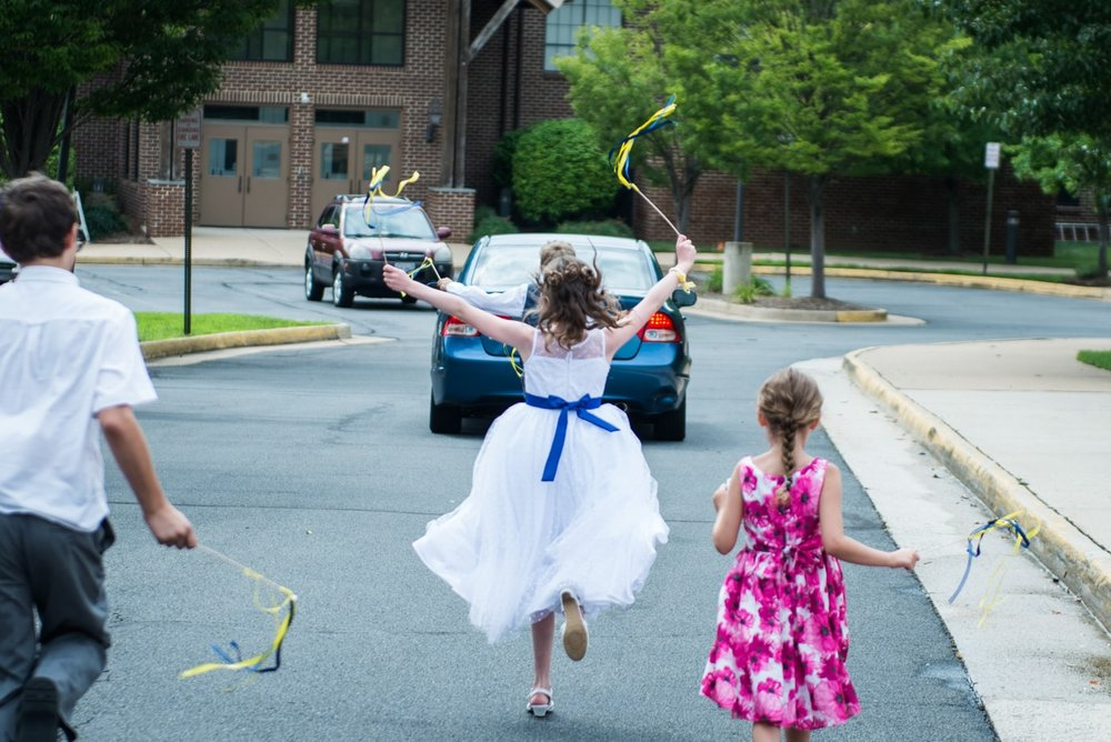 Kids chase after the car carrying the bride and groom after their wedding reception at St Mark Catholic Church in Vienna, Virginia